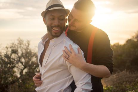 Stylish gay couple hugs overlooking ocea