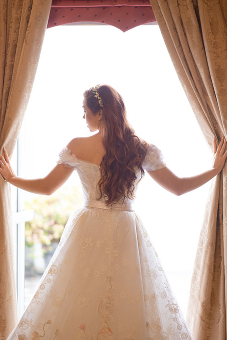 Redhead bride silhouetted in open window
