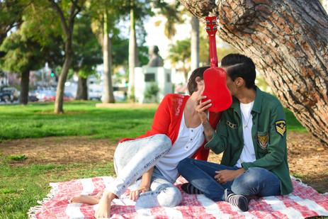 Lesbian couple kissing behind red ukulel