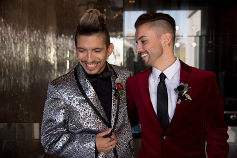Fashionable grooms laugh together