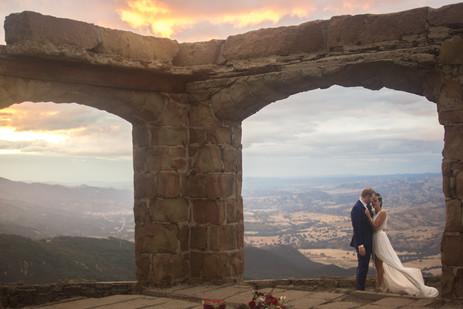Newlywed couple in wedding attire high a