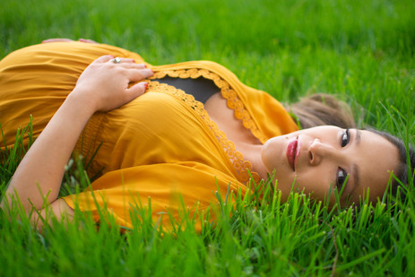 Pregnant woman in yellow dress lies in g