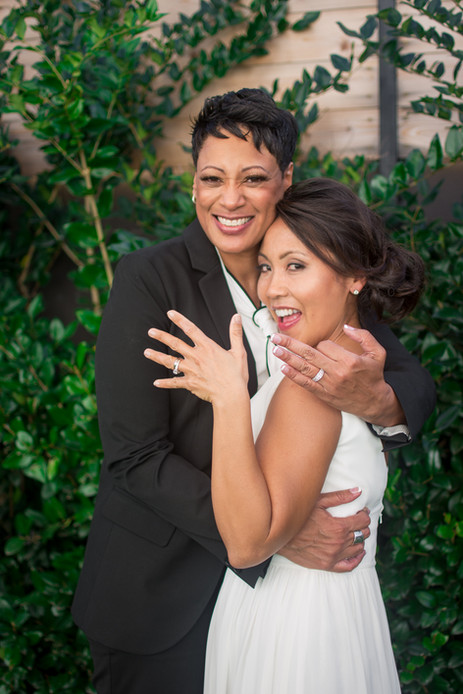 Lesbian brides smile and show off rings