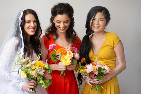Bride laughing with bridesmaids in orang