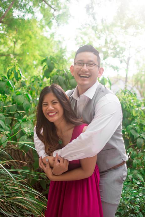 Man hugs woman in pink dress in garden