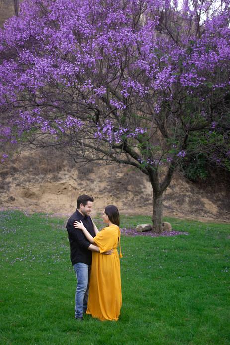 Pregnant woman in yellow dress hugs man