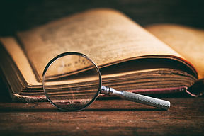 Vintage book and magnifying glass on woo