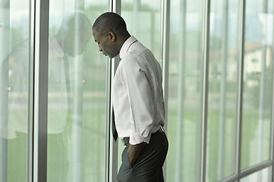 A Stressed Business Man Rests His Forehead Against An Office Window