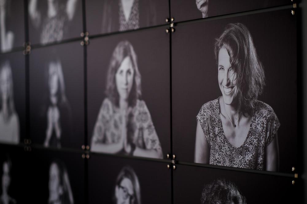 Een wall of fame met professionele foto's van medewerkers zorgt voor teamspirit op kantoor.