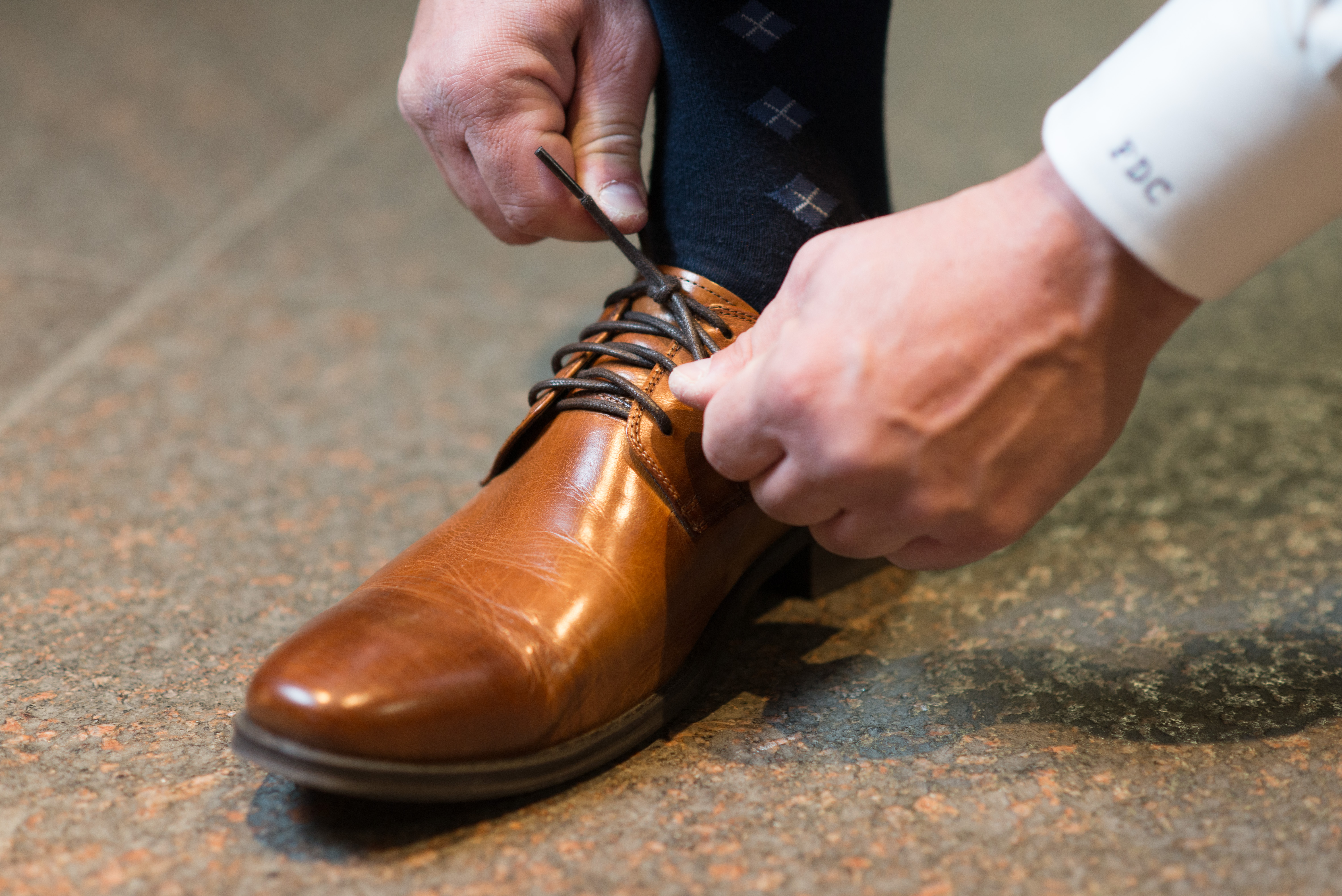 Man Tying Brown Dress Shoe