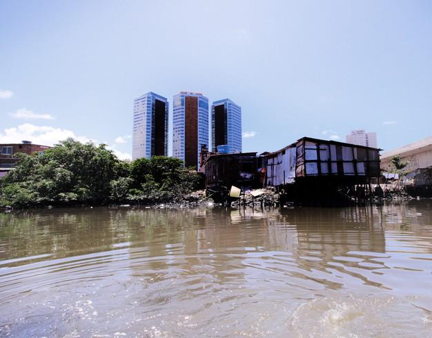 prédios sofisticados contrastam com casa pobre e rio que recebe esgoto