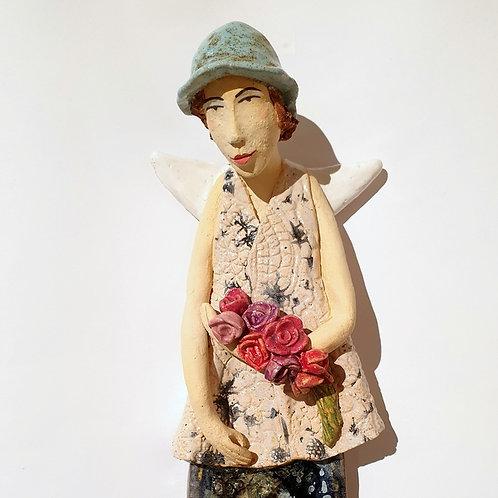 Anioł w kapeluszu z kwiatami