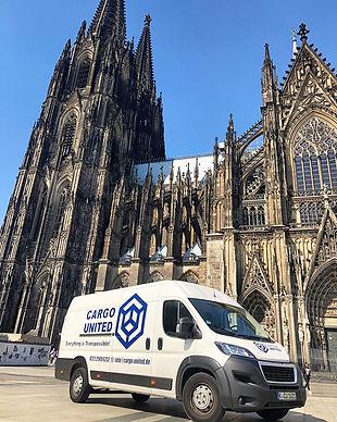 Transporter vor dem Kölner Dom. Weißer Transporter mit blauer beschriftung.