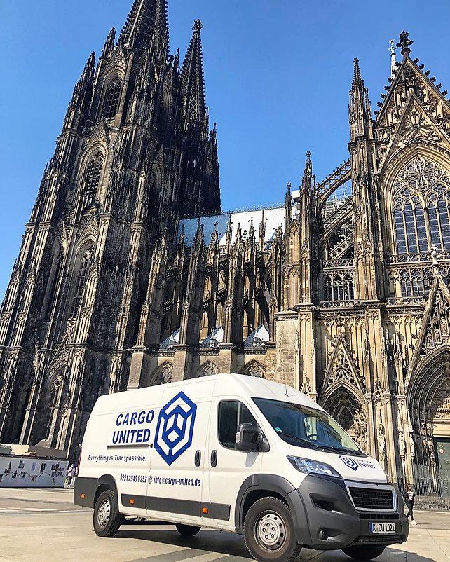 Transport Fahrzeug vor dem Kölner Dom. Der Transporter ist weiß und blau beschriftet.