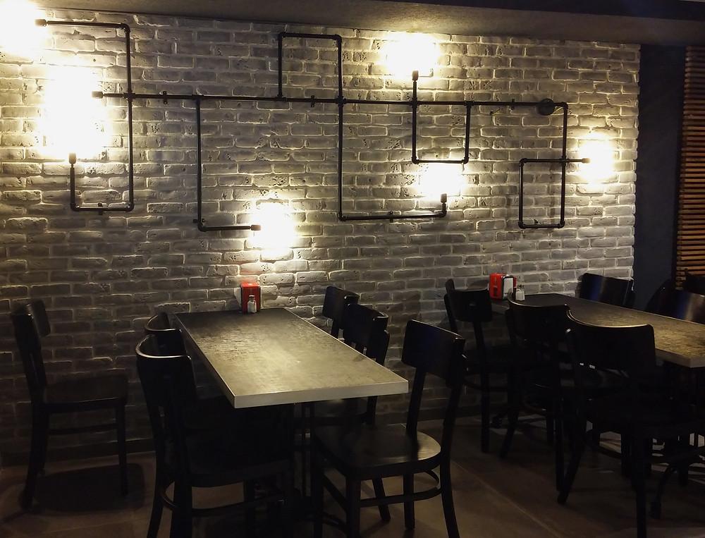מנורת צינורות על קיר בריקים