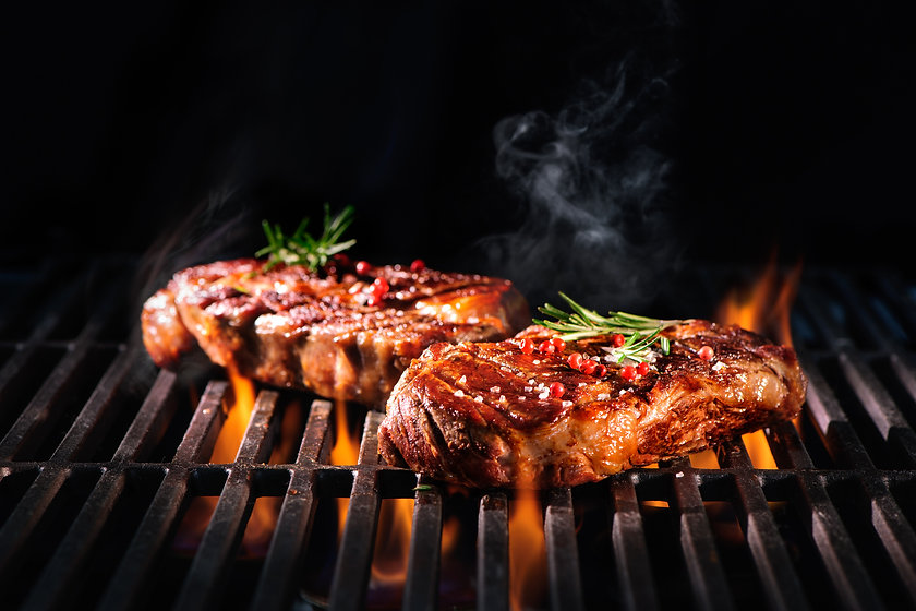 Beef steaks on the grill with flames.jpg