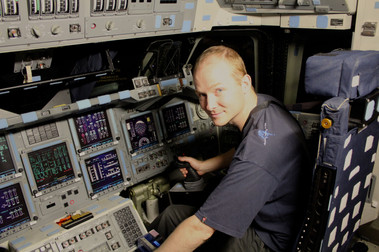 at the controls of the space shuttle Atlantis.