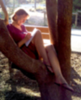 Author Liane Carter  writing sitting in a tree.