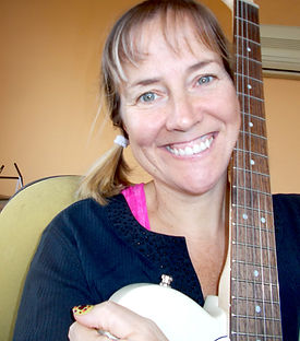 Author Liane Carter Bio image holding guitar.