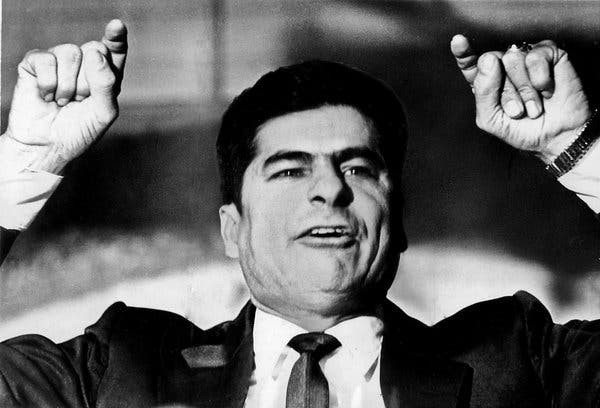 Black and white photo of Reijes Tijerina, a Chicano male wearing a suit and raising his hands and pointing his pointer fingers at an audience