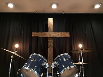 A picture of drums with a wooden cross behind it. The background is black.