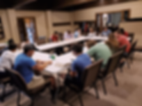 A photo of people sitting around four tables in the shape of a rectangle during bible study.