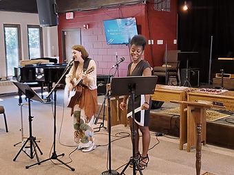 A photo of two women, one holding a guitar, singing in the sanctuary.