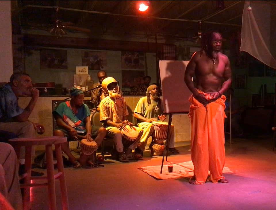 Man stands in a dark, red light lit room wearing jail uniform in front of empty painting canvas with drummers behind him and audience members looking on