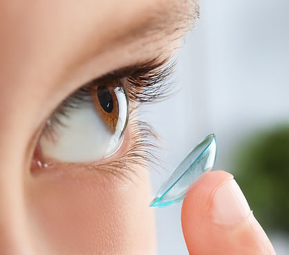Little child putting contact lens into h