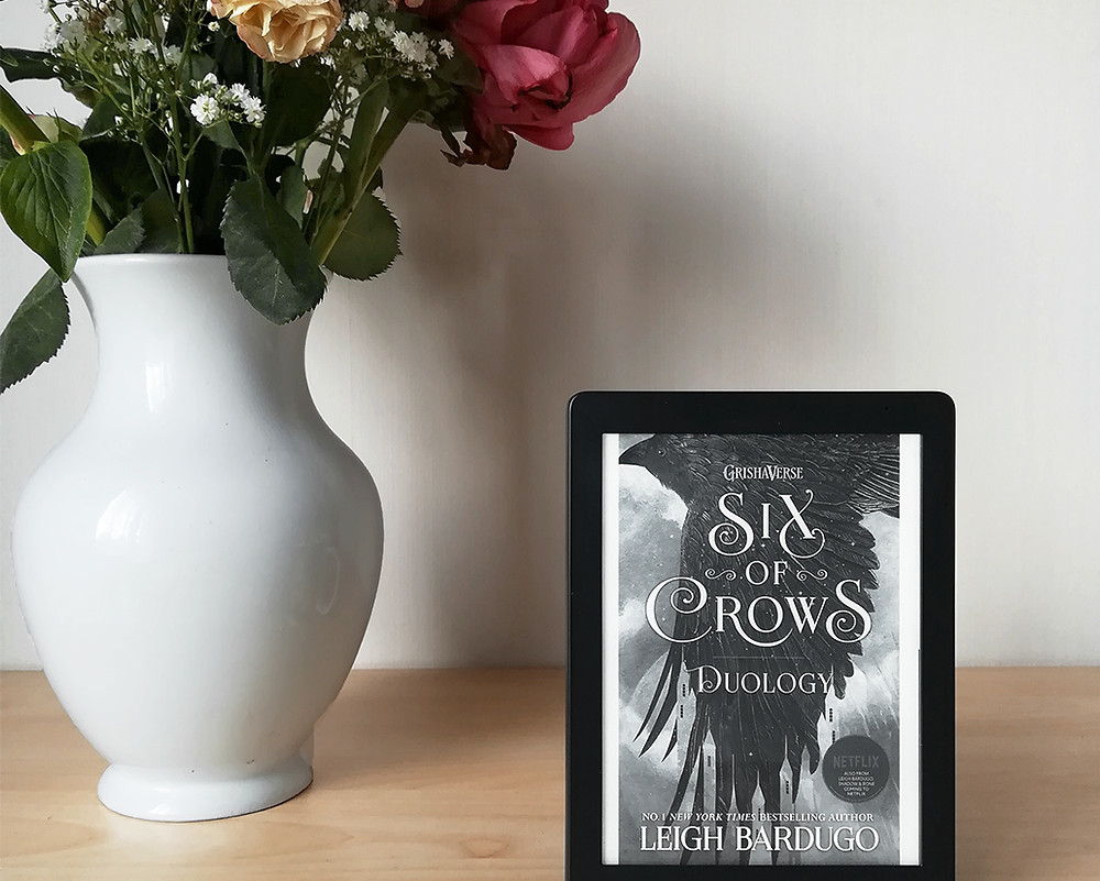 An e-reader showing the cover of the book is standing on a table next to a bunch of red and white flowers in a white vase.