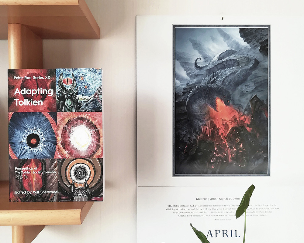 """a copy of """"Adapting Tolkien"""" is propped against the end of a shelf. On the wall next to it is the 2021 Tolkien Calendar with a picture by John Howe. A few leaves appear in the bottom right-hand corner."""