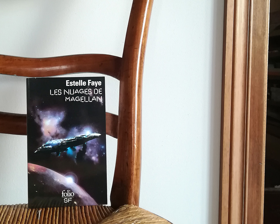 The book, showing a cover illustration in tones of blue and purple, is set on an old chair in front of a white wall.