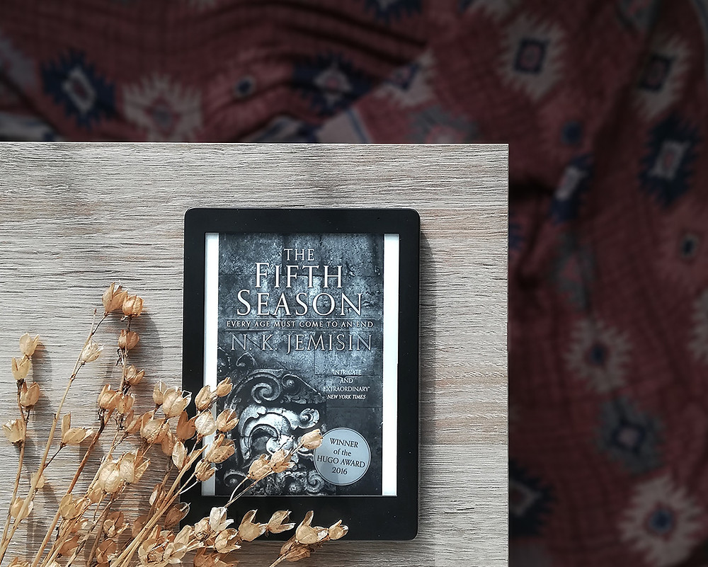 An e-reader showing the book cover is resting on a wooden table, with a warm-toned fabric in the background.