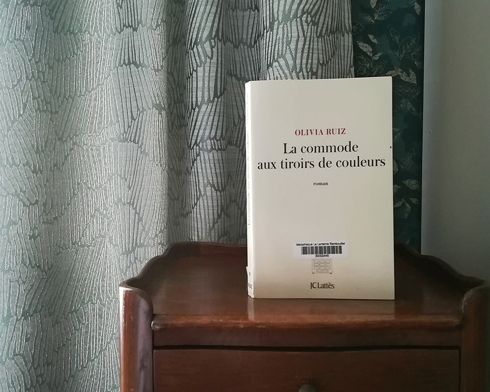 Un livre posé sur une table de chevet en bois sombre, devant un rideau d'une teinte gris-vert claire.