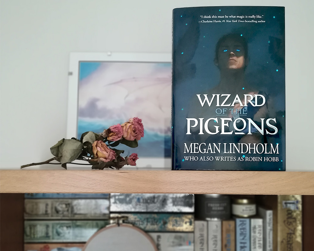Le livre est posé à la verticale sur le haut d'une bibliothèque, à côté de roses séchées. A l'étage en-dessous sont rangés des livres de Robin Hobb et une broderie dans un tambour circulaire.