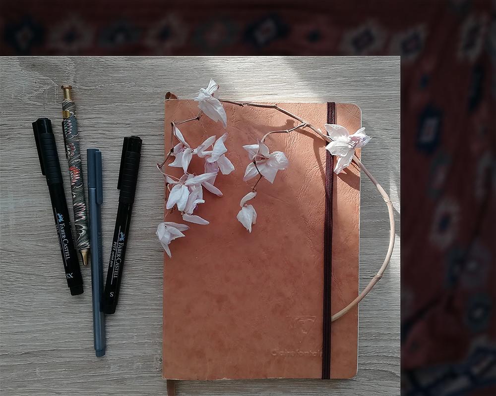 Un carnet et quatre stylos sont posés sur une table en bois. Une fleur séchée est coincée dans l'élastique du carnet.