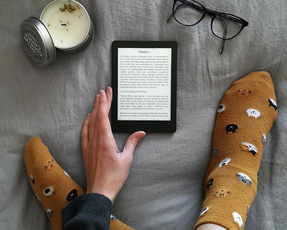 The reader's hand and feet on a bed, surround an e-reader showing the first page of the book. A candle and a pair of glasses are added to the composition.