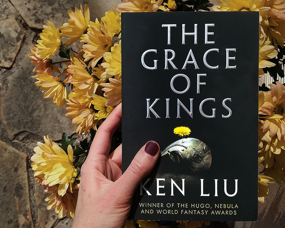 a white hand holding the book above a flower pot with yellow blossoms.