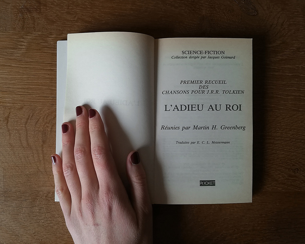 a white hand with nails painted in a dark colour, holds the book open at the title page, over a woodden table.