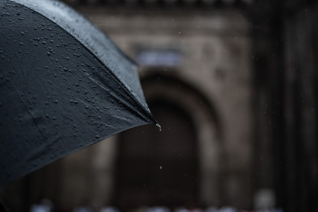 A dark umbrella, hiding its owner, with a blurry building in the background.