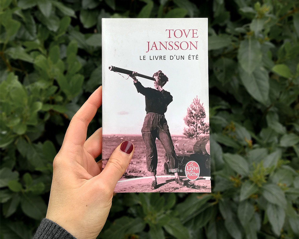 A white hand holding the book in front of a dark-leafed bush.