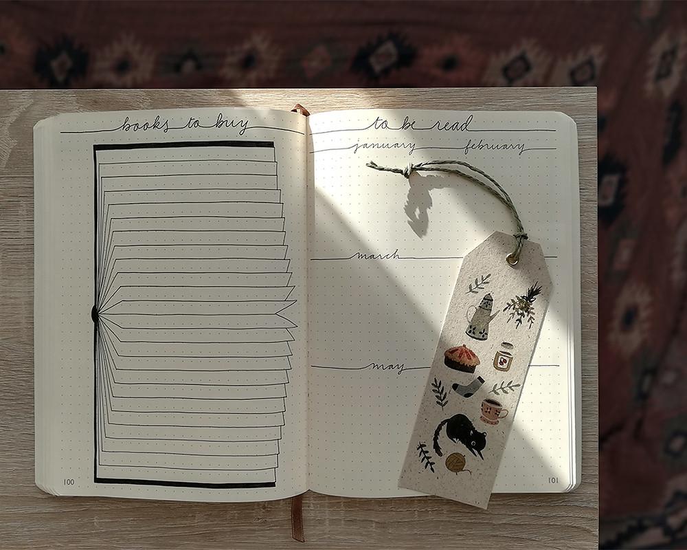 """Un carnet ouvert. Une page s'intitule """"books to buy"""" et l'autre """"to be read"""". Un rayon de soleil traverse la page de droite et tombe sur un marque-page."""
