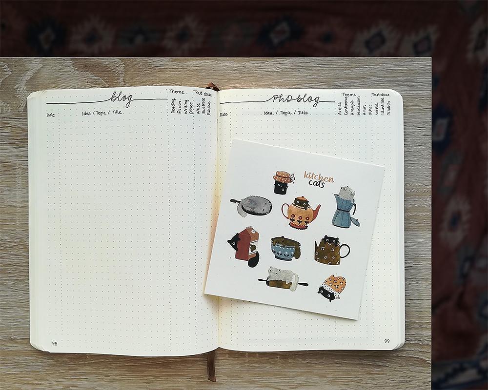"""Un carnet ouvert. La page de gauche s'intitule """"blog"""" et celle de droite """"PhD blog"""". Une illustration montrant des chats est posée sur la page de droite."""