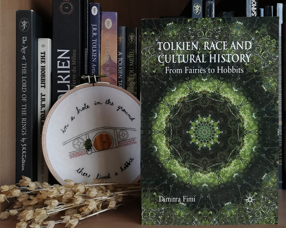 a copy of the book is standing on a shelf in front of Tolkien-realted book and the embroidery of a Hobbit front door.