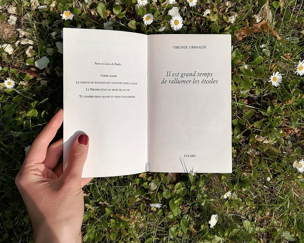 Awhite hand with dark red nail polish holds the book open on a patch of grass dotted with daisies.