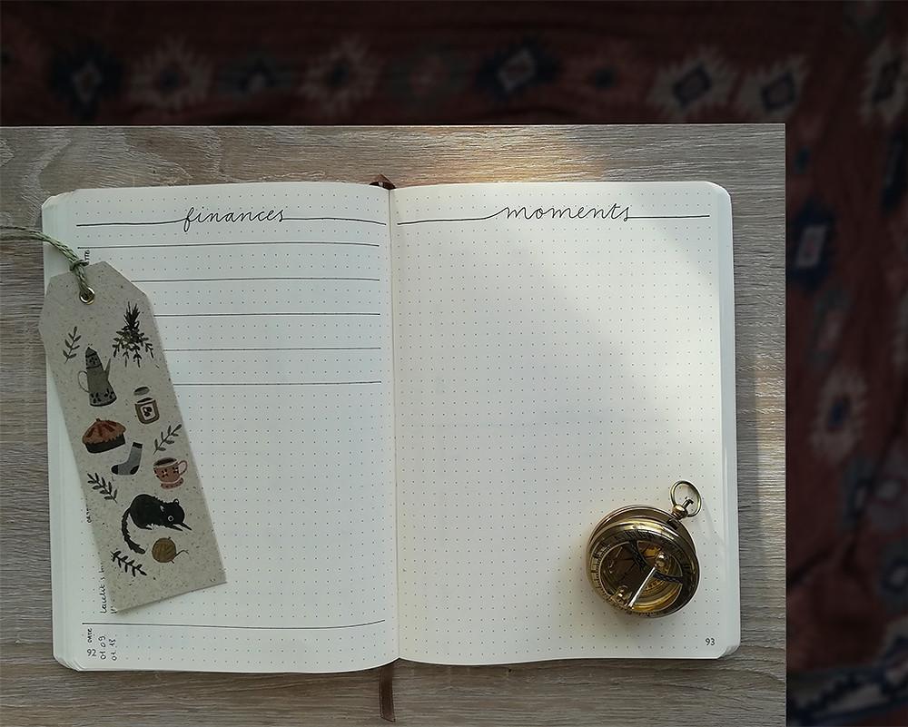 """Un carnet ouvert. La page de gauche s'intitule """"finances"""" et celle de droite """"moments"""". Un marque-page illustré et une boussole sont posés sur les pages."""