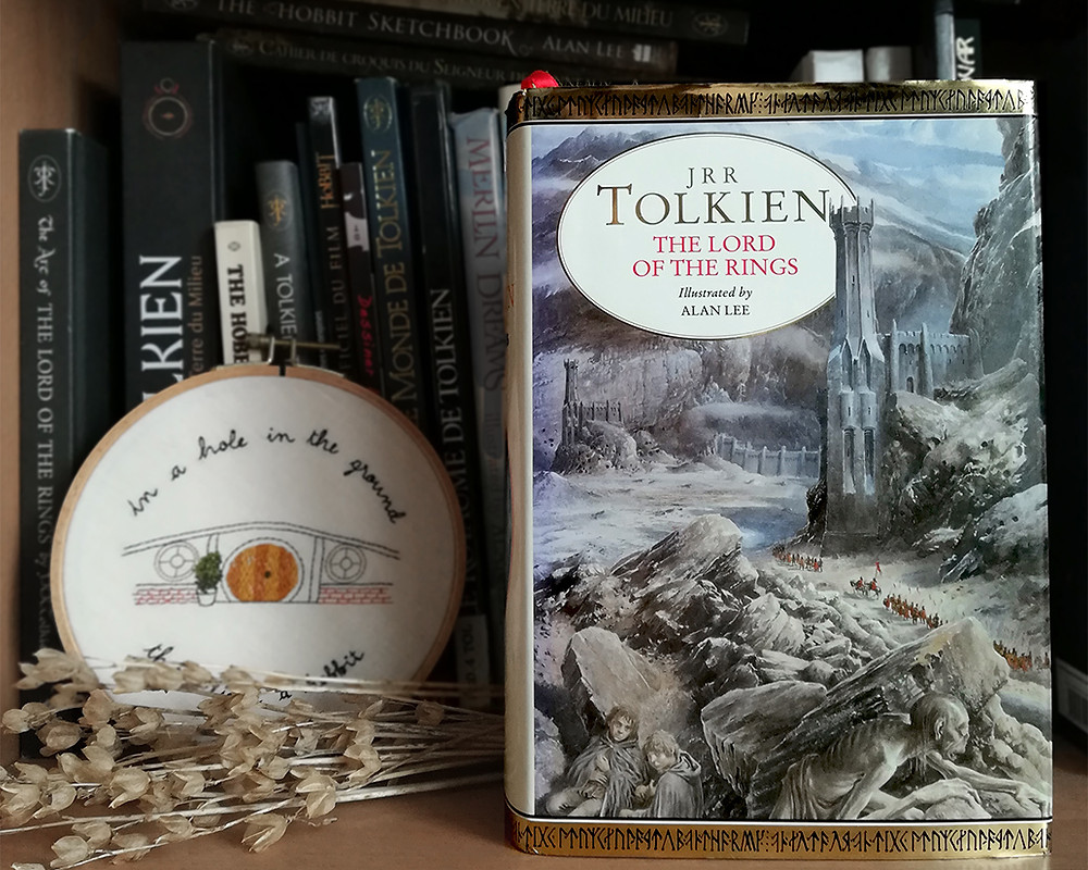 A one-volume copy of The Lord of the Rings, with a cover illustrated by Alan Lee, sitting on a shelf with other Tolkien books. An embroidery showing a Hobbit hole is peeking behind the book, as well as a bunch of dried flowers.