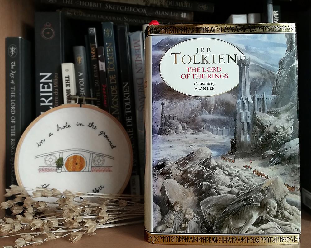 Une copie de l'édition en un volume du Seigneur des Anneaux en anglais, avec la couverture illustrée par Alan Lee, se tient sur une étagère devant d'autres livres concernant Tolkien. Une broderie montrant Cul-de-Sac apparaît juste derrière, ainsi qu'un bouquet de fleurs séchées.