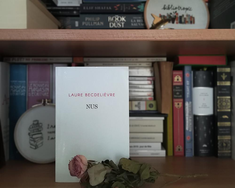 Une copie du livre est posée debout devant une bibliothèque. Une branche de rosier rompt la monotonie de la couverture blanche.