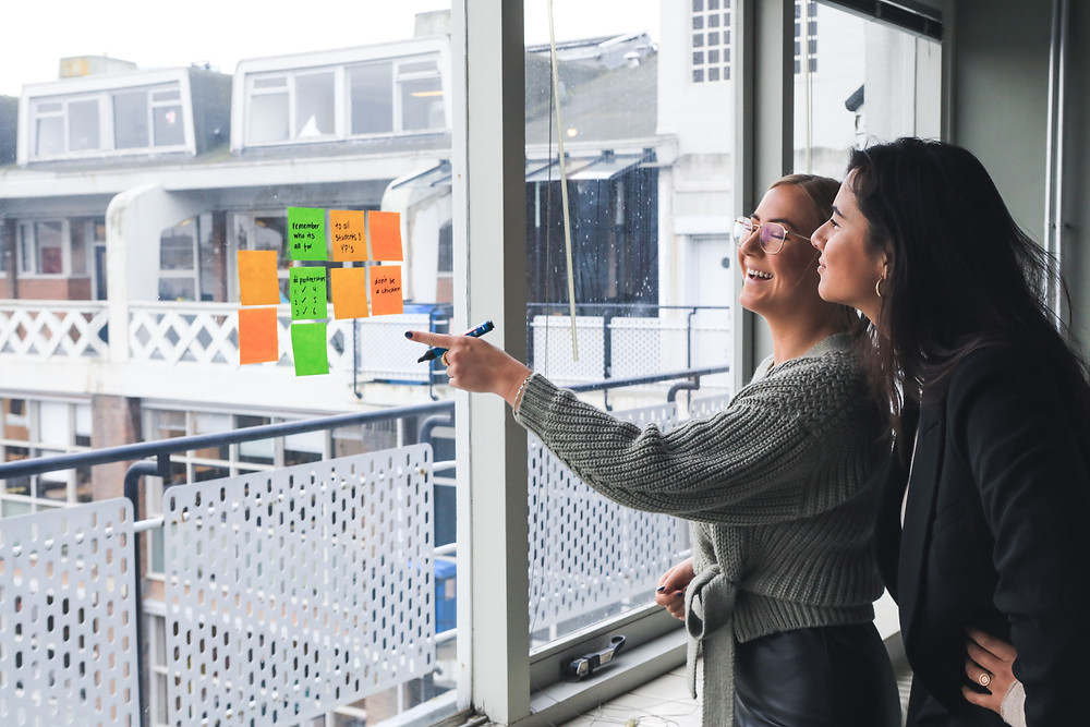 Two women smiling, looking at post-it notes on window